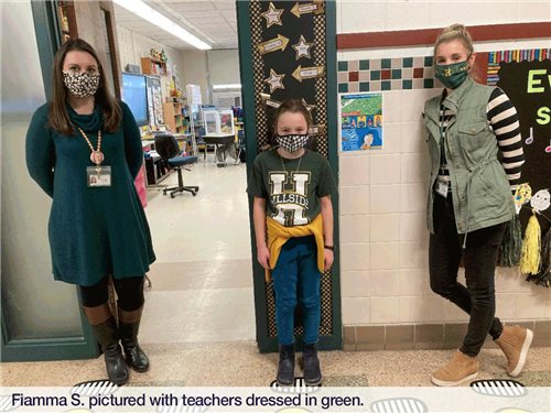 Fiamma S. pictured with teachers dressed in green.
